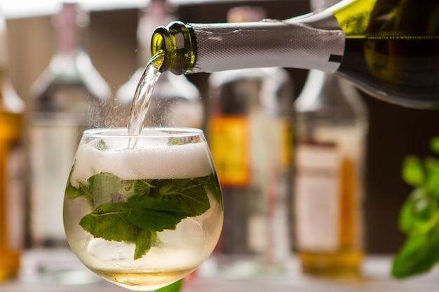La bouteille verse le liquide dans le verre. a boire avec des feuilles de menthe. cocktail hugo préparé au bar. eau minérale et champagne.