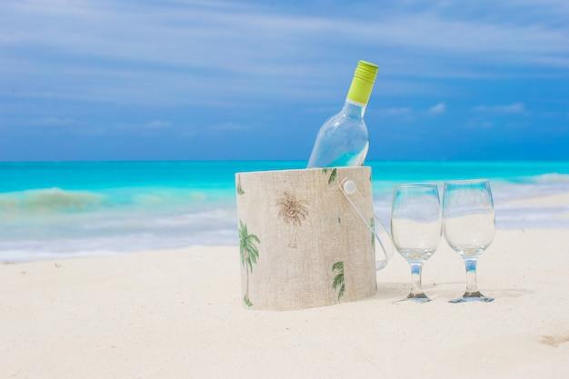 Bouteille de vin blanc et deux verres sur la plage de sable exotique