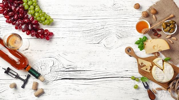 Bouteille de vin blanc, raisin, miel, fromage et verre à vin sur planche de bois blanc. vue de dessus avec espace de copie.