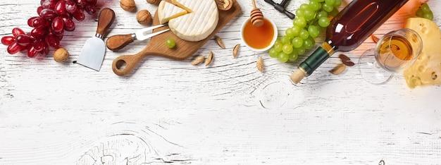 Bouteille de vin blanc, raisin, miel, fromage et verre à vin sur planche de bois blanc. vue de dessus panoramique avec espace de copie pour votre texte.