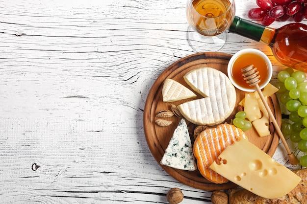 Bouteille de vin blanc, raisin, miel, fromage et verre à vin sur une planche en bois blanche
