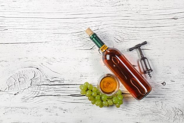 Bouteille de vin blanc, raisin et verre à vin sur un fond en bois blanc