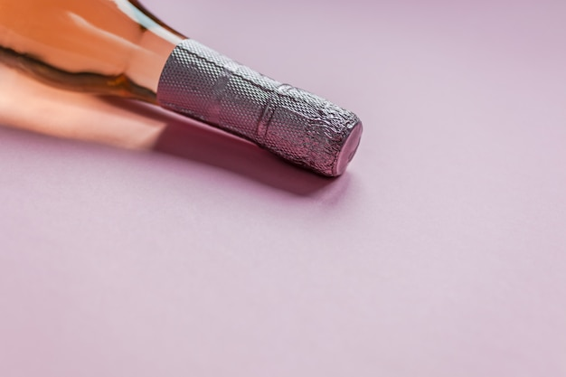 Bouteille de vin de champagne rose sur fond rose