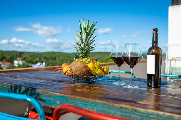 Bouteille de vin avec deux verres et une assiette de fruits exotiques