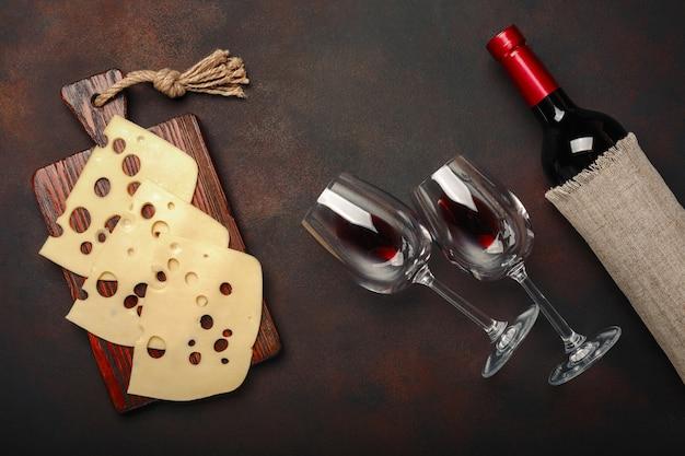 Bouteille de vin, deux verres et du fromage maasdam tranchés sur une planche à découper sur fond rouillé