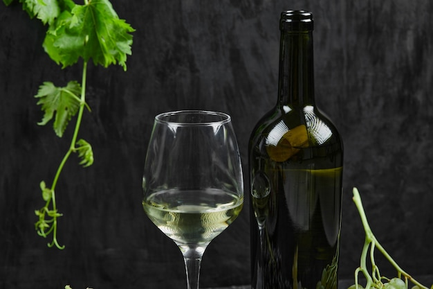 Une bouteille de vin sur un espace sombre.