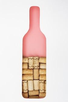 La bouteille de vin est remplie de bouchons de vin. figure en papier de bouteille. concept pour bar à vin, restaurant. vin rose ou rosé créatif. copiez l'espace.