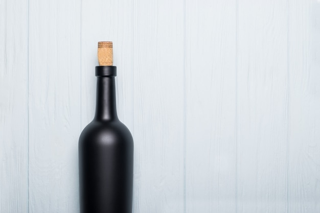 Bouteille de vin sur un fond en bois blanc