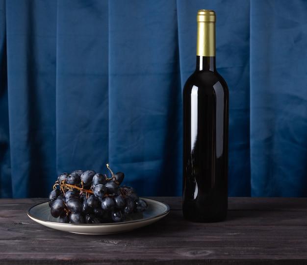 Une bouteille de vin et de raisins sur une assiette sur un fond ondulé en tissu.