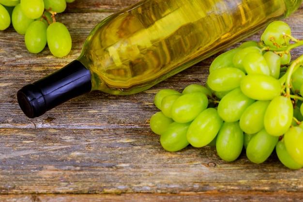 Bouteille de vin, raisins et bouchons de liège sur fond de vin de table en bois