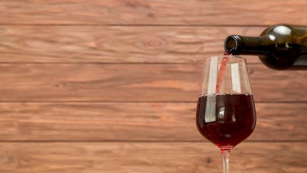 Une bouteille de vin remplissant le verre à vin