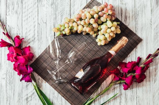 Bouteille de vin rosé avec verres et raisins