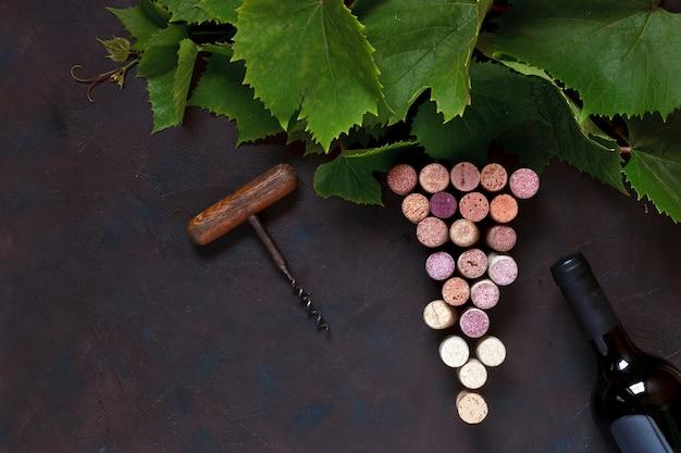 Une bouteille de vin rouge, bouchons de liège, tire-bouchon et feuilles de vigne.
