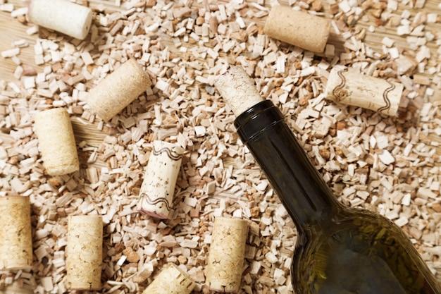 Bouteille de vin rouge avec des bouchons en liège sur une vieille table en bois avec de la sciure de bois dispersée.