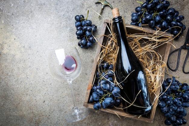 Une bouteille de vin rouge dans une boîte avec des raisins sur une pierre grise