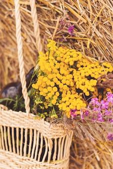 Bouteille de vin rouge, deux verres et fleurs sauvages dans un panier sur le terrain et gerbe. un rendez-vous romantique.