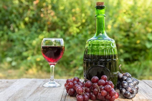 Une bouteille de vin rouge et une grappe de raisin