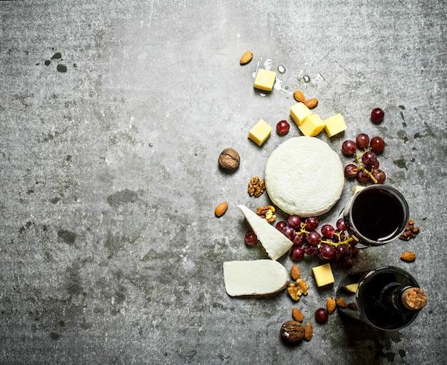 Bouteille de vin rouge avec des noix et du fromage. sur la table en pierre.
