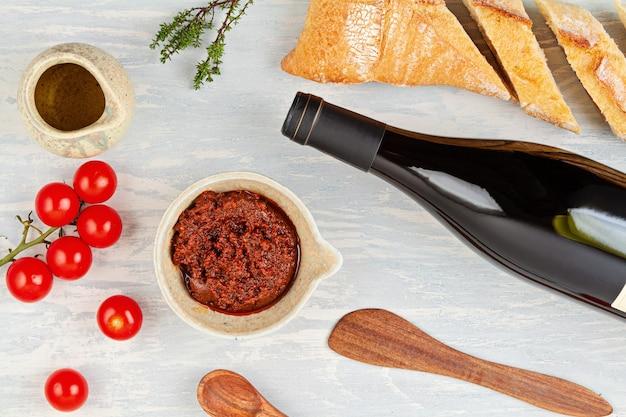 Bouteille de vin rouge, pain et tomates pour buffet. le français ou l'italien traditionnel propose une pose à plat. vue de dessus