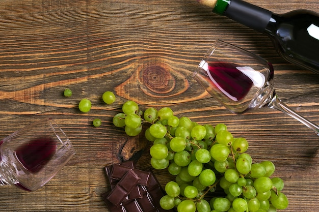 Bouteille de vin rouge raisin chocolat et verres sur table en bois vue de dessus avec espace de copie