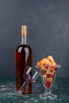 Bouteille de vin rouge, raisins et verre de fruits mélangés sur table en marbre.