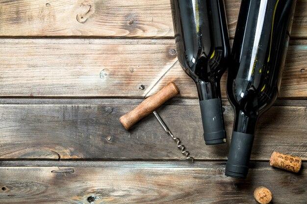 Bouteille de vin rouge avec un tire-bouchon. sur un bois.