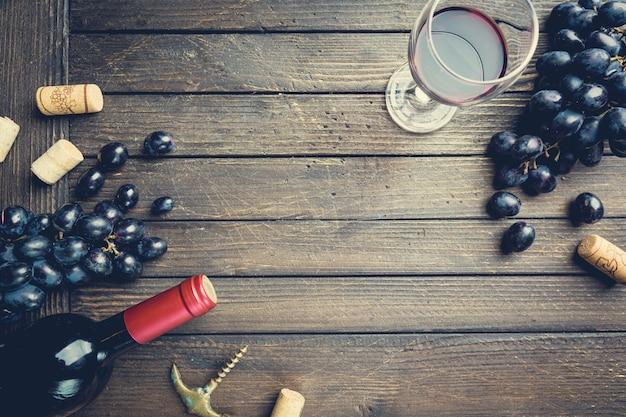 Une bouteille de vin rouge avec verre et raisins sur bois