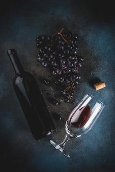 Bouteille de vin rouge avec verre et raisins