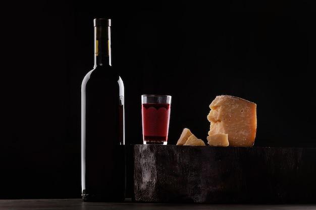 Une bouteille de vin rouge et un verre de vin rouge, une sorte de fromage cher avec de la moisissure et des raisins. sur fond noir. place pour le logo.