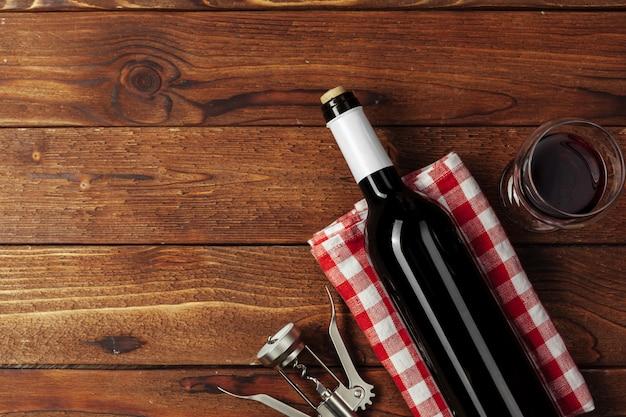 Bouteille de vin rouge, verre à vin et tire-bouchon sur table en bois