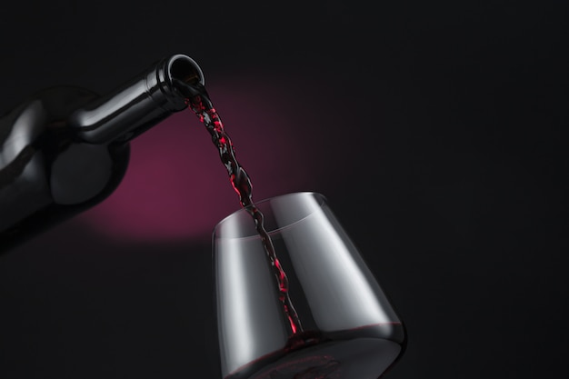 Bouteille de vin rouge versée dans le verre à vin