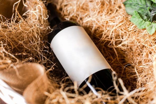 Une bouteille de vin rouge vue de face sur le foin