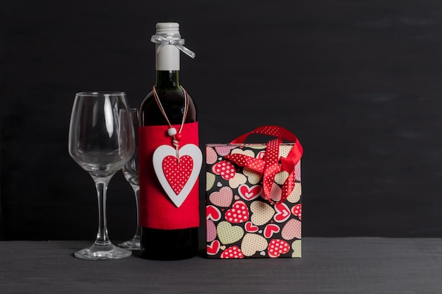 Bouteille de vin, sac à provisions, boîte blanche et coeur rouge de la saint-valentin sur fond noir