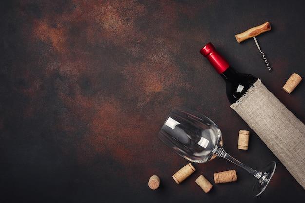 Bouteille de vin, tire-bouchon et bouchons en liège, sur la vue de dessus de fond rouillé