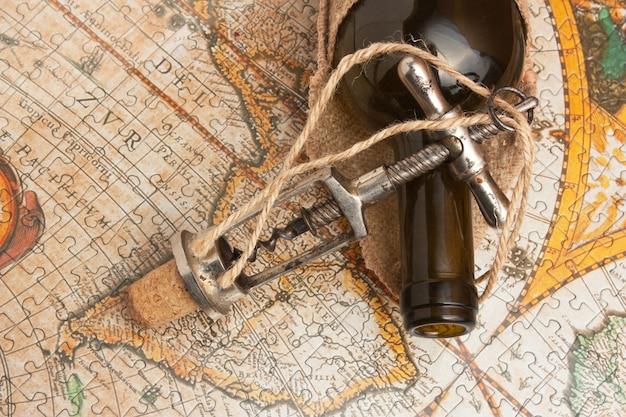 Bouteille de vin et un tire-bouchon sur le fond de vieilles cartes