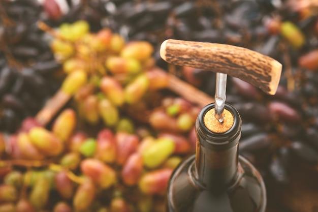 Bouteille de vin avec tire-bouchon. ouverture d'une bouteille de vin avec un tire-bouchon dans un restaurant. composition de vin sur fond rustique sombre avec espace de copie. maquette.