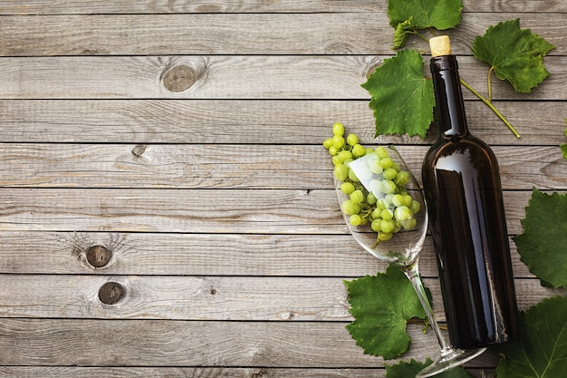 Bouteille de vin avec un verre et une grappe de raisin sur une table en bois avec espace copie