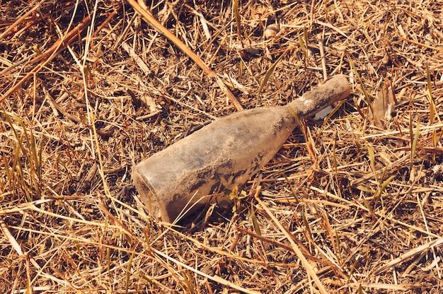 Bouteille de vin en verre et poubelles dans la forêt. pollution environnementale. problème environnemental et catastrophe.