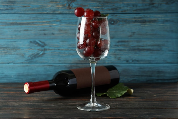 Bouteille de vin, verre de raisin et feuille sur table en bois