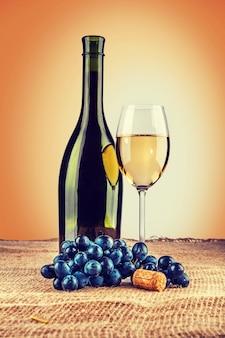 Bouteille de vin et verre à vin avec branche de raisin sur toile de jute instagram stile