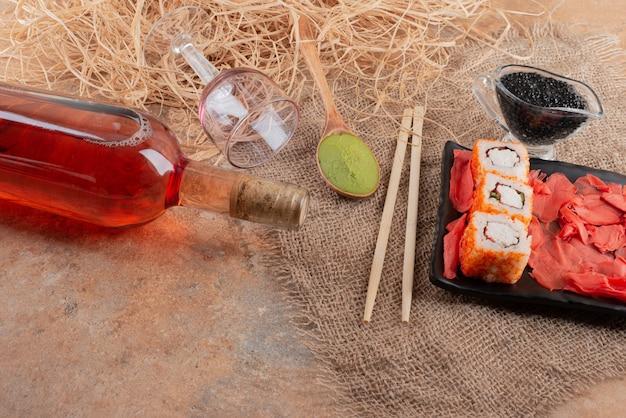 Bouteille de vin avec verre à vin et sushi sur toile de jute