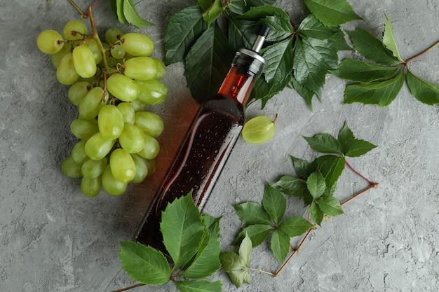 Bouteille de vinaigre, de raisin et de feuilles sur une table texturée grise