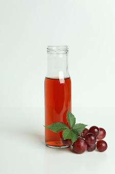 Bouteille de vinaigre et raisin sur tableau blanc