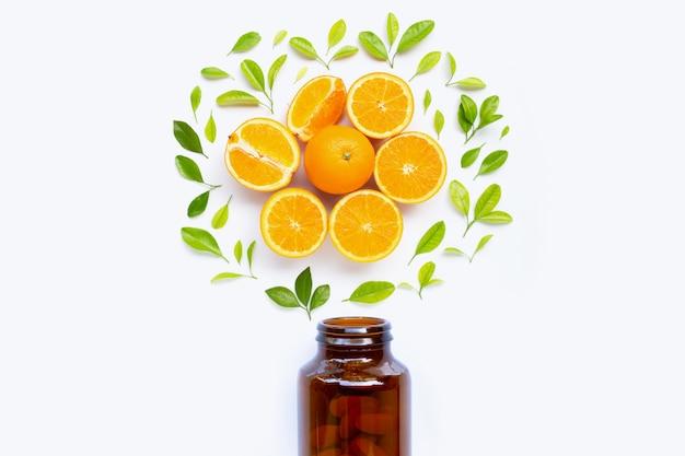 Bouteille de vitamine c et des pilules avec des fruits orange sur blanc