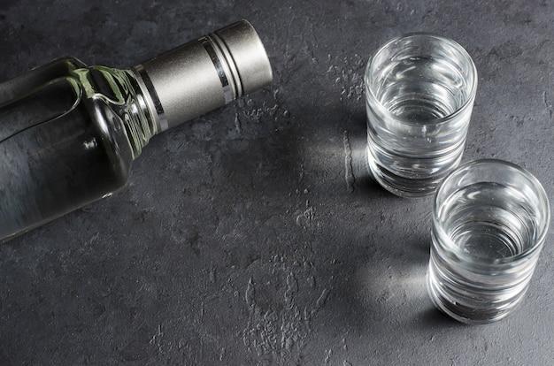 Une bouteille de vodka et deux verres. espace de copie