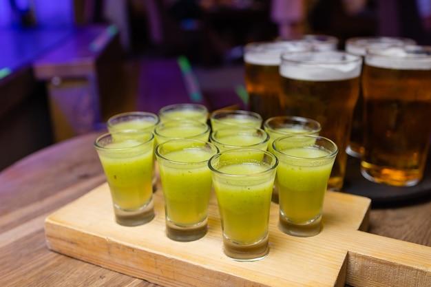 Bouteille de vodka avec verres à liqueur et tranches de citron. sur fond de pierre sombre.