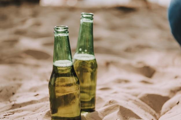Bouteilles de bière lager dans le sable à la fête sur la plage