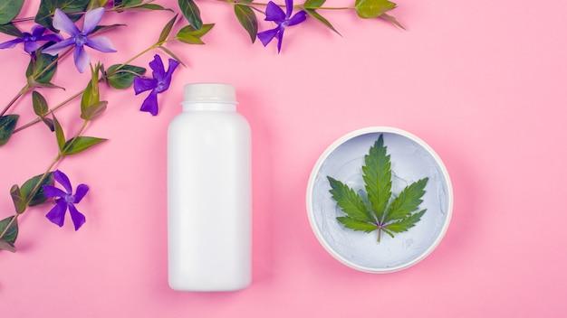 Bouteilles blanches avec des cosmétiques sur fond rose avec une feuille de marijuana et de fleurs sauvages violettes vue de dessus. beauté, soins de la peau.