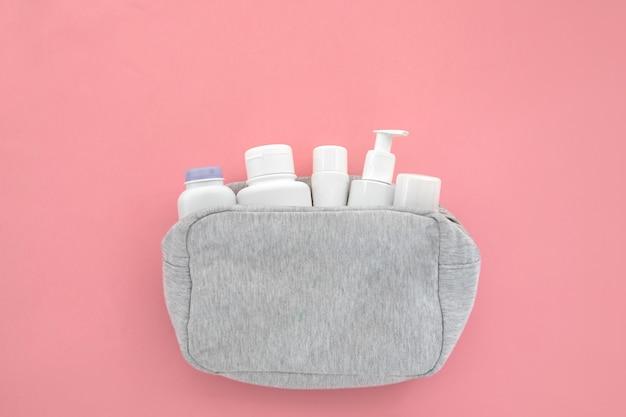 Bouteilles blanches de produits cosmétiques nettoyants dans un sac à cosmétiques