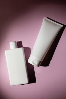 Bouteilles blanches de shampoing et de lotion sur fond rose, maquettes pour la conception